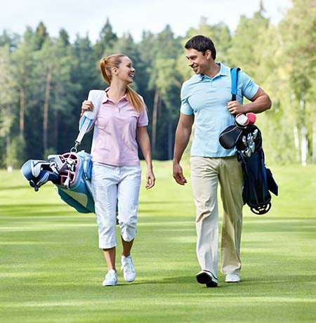 A couple takes a stroll on a golf course
